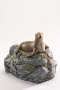 A serene sea lion atop mossy rocks - a custom cremation urn by Une Belle Vie artists